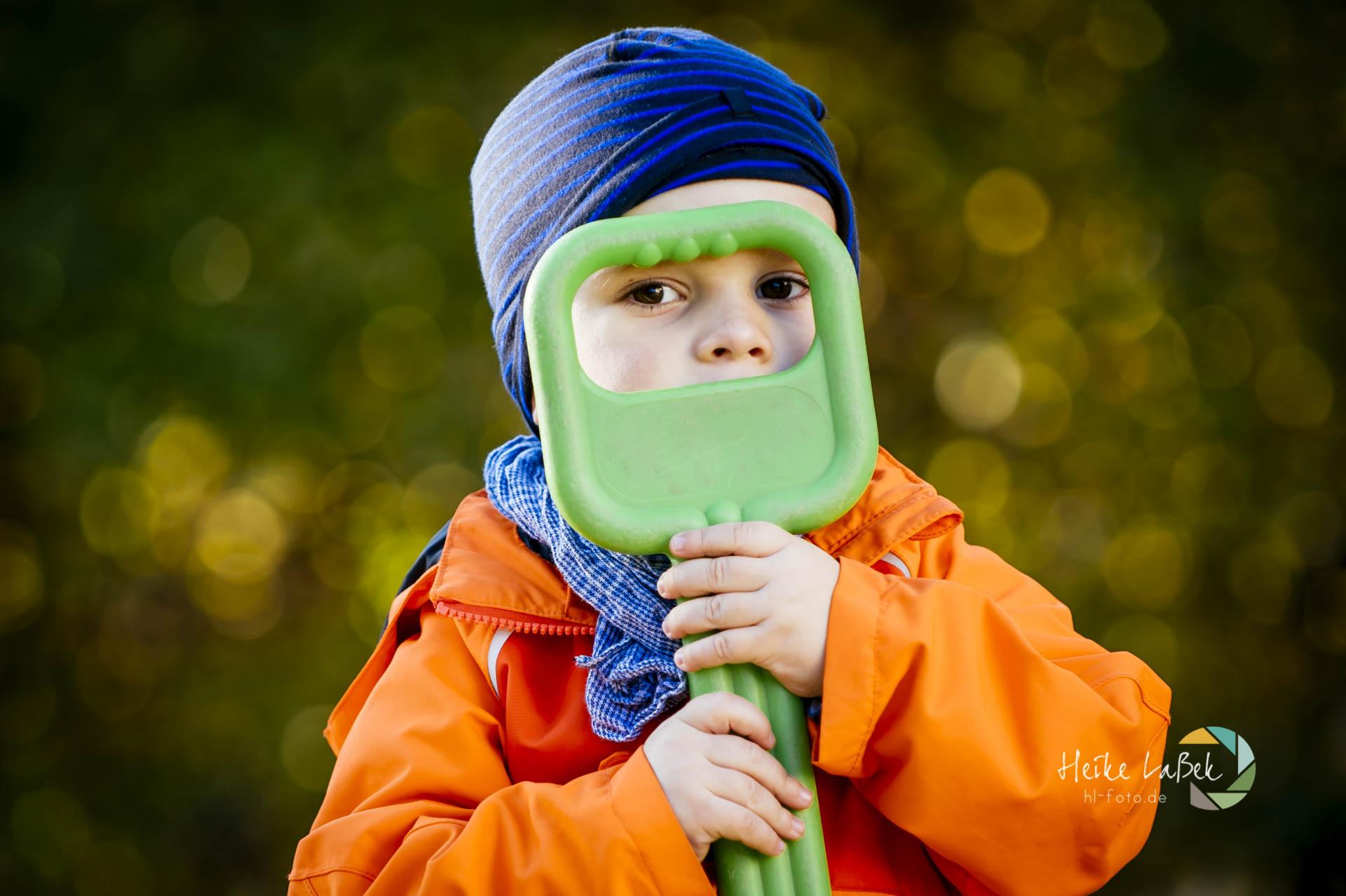kleiner Junge sieht durch den Griff seiner Schaufel